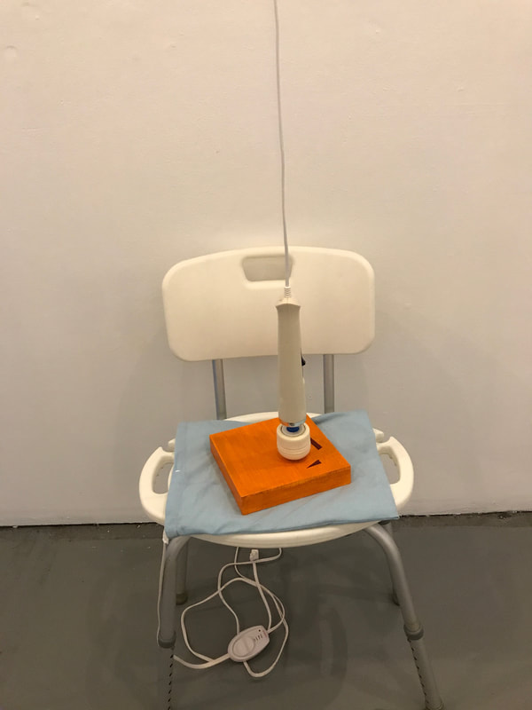 Image Description: A white shower chair with silver metallic legs placed in front of a wall. Seated on it is a light blue heating pad, with a small wood board painted orange with two deep red geometric shapes. On top of it is a white headed handheld massager hanging from the ceiling, slightly caressing the surface of the wood board.